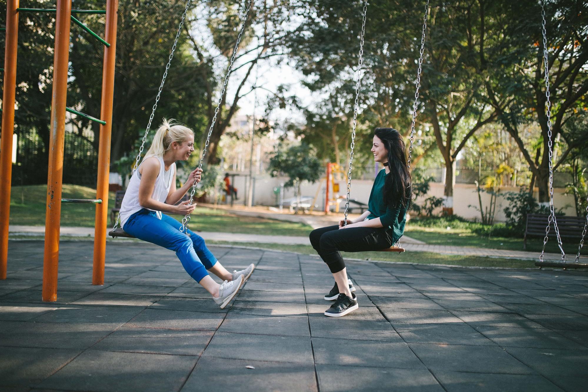 women talking on swings